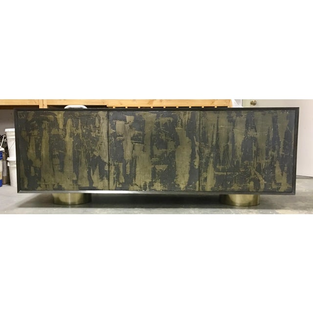 A Bridges Over Time brass and iron coated credenza by Marco Antonio. It is beautifully decorated like a painting on the...