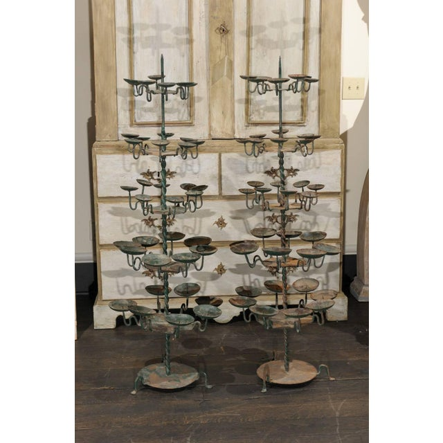 Two Spanish large size candle trees. This 19th century pair of Spanish metal candle trees features a multi-tiered spread...