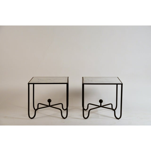 Chic pair of wrought Iron and marble 'Entretoise' side tables by Design Frères. Matte black wrought iron bases with honed...