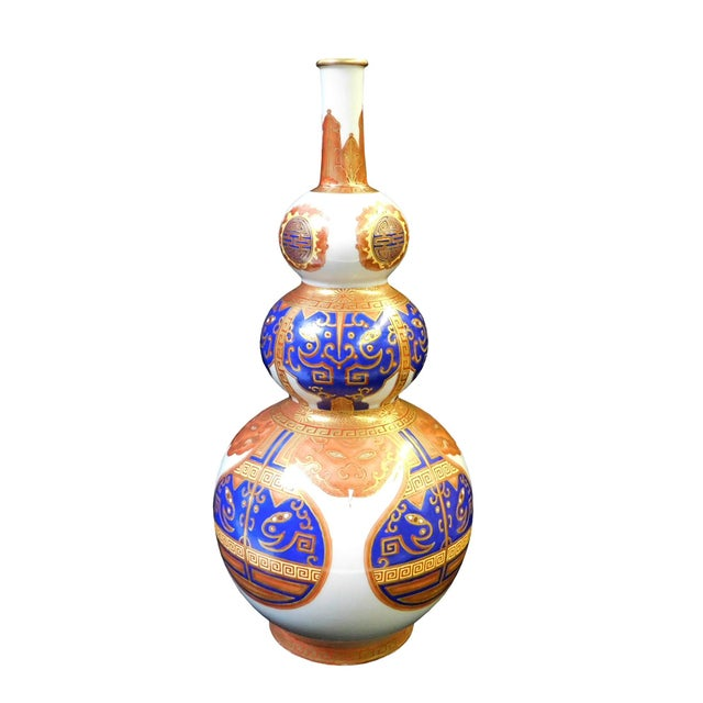 This is a Chinese decorative porcelain vase in white base color with golden orange and blue color graphic. Depicts an...