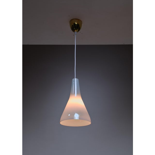 A model 61-363 glass pendant lamp by Lisa Johansson-Pape for Orno in rare to find mother of pearl glass, giving a...
