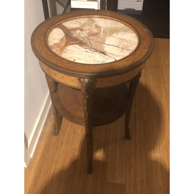 This amazing and unique side table was handed down through generations. The side table is round and also has a shelf.