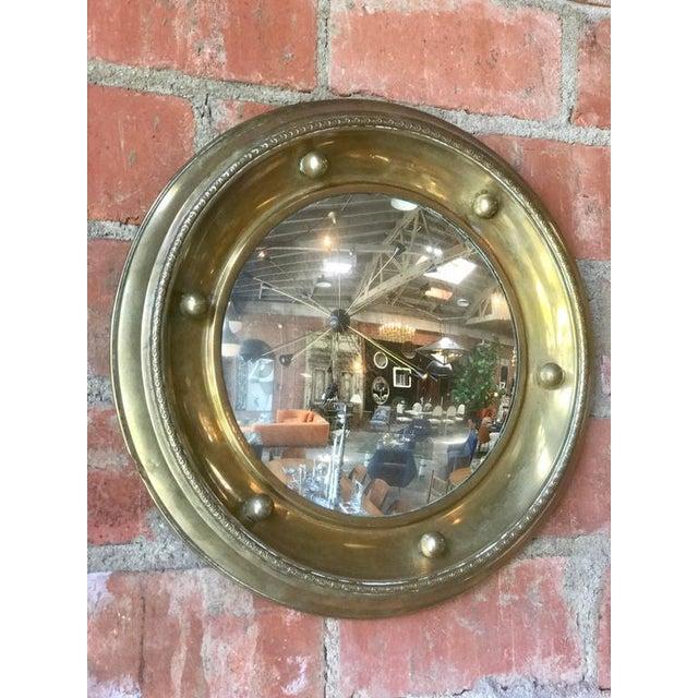 Antique brass round wall mirror.