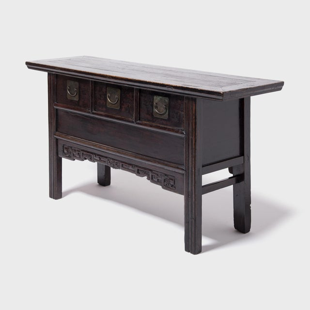 The sleek design of this 19th century three drawer table is generally attributed to the minimal style of the Ming period...