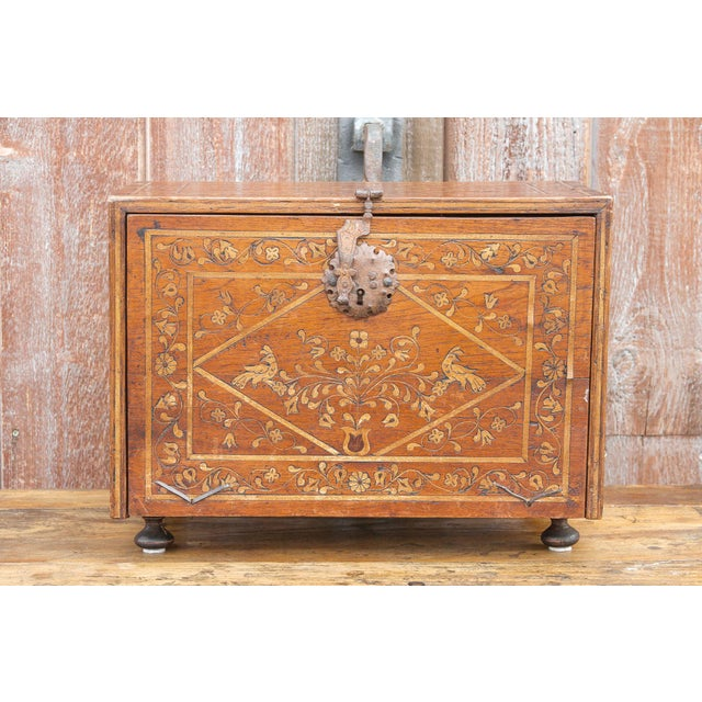 A spectacular table top Bergueno with marquetry inlaid designs depicting vine leaf motif on its exterior, with the...