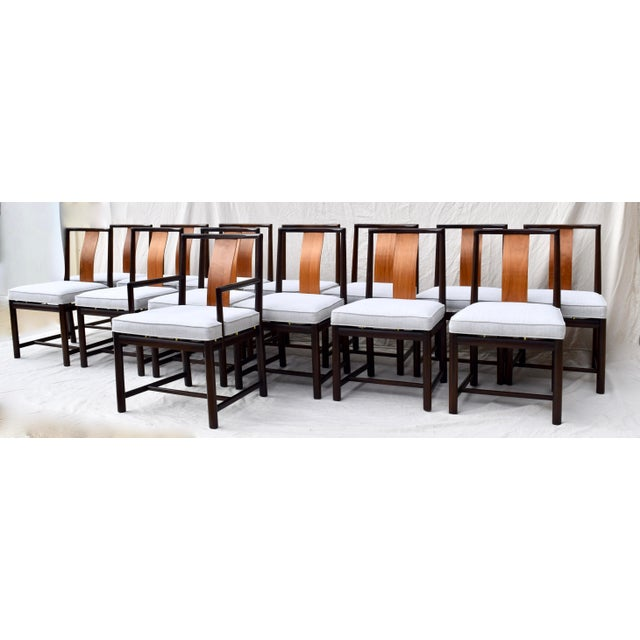 A striking set of 14 John Stuart dining chairs of dark mahogany and walnut, consisting of 13 side chairs and one captains...