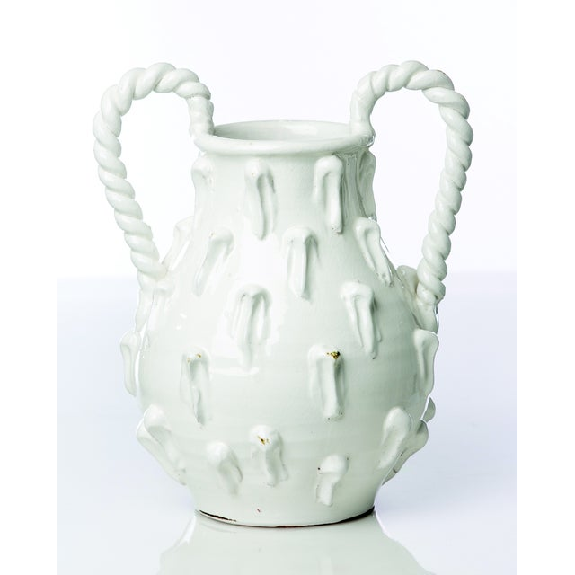 A striking white glazed jug with interesting texture and braided terracotta handles. Perfect for most any arrangement in...