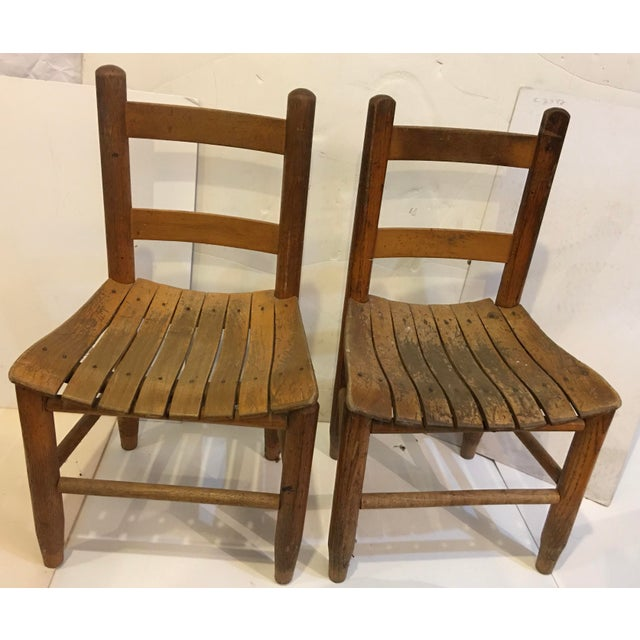 A wonderful pair of Upstate New York country vintage children's chairs in decent shape overall. Some of the varnish faded....