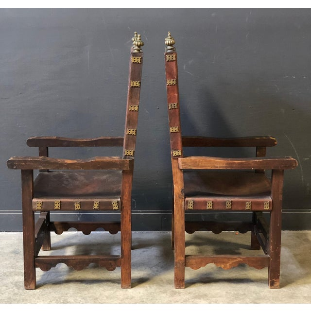 Antique Spanish Revival hand carved chairs with thick leather seat and back, brass detailing throughout. These large...