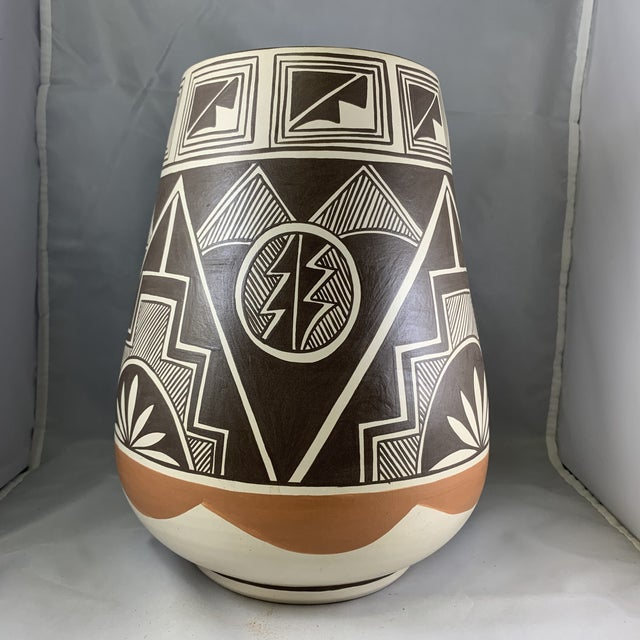 Tall Southwestern Polychrome Painted vase featuring a geometric mountain design. The vase is signed by the artist Stella...