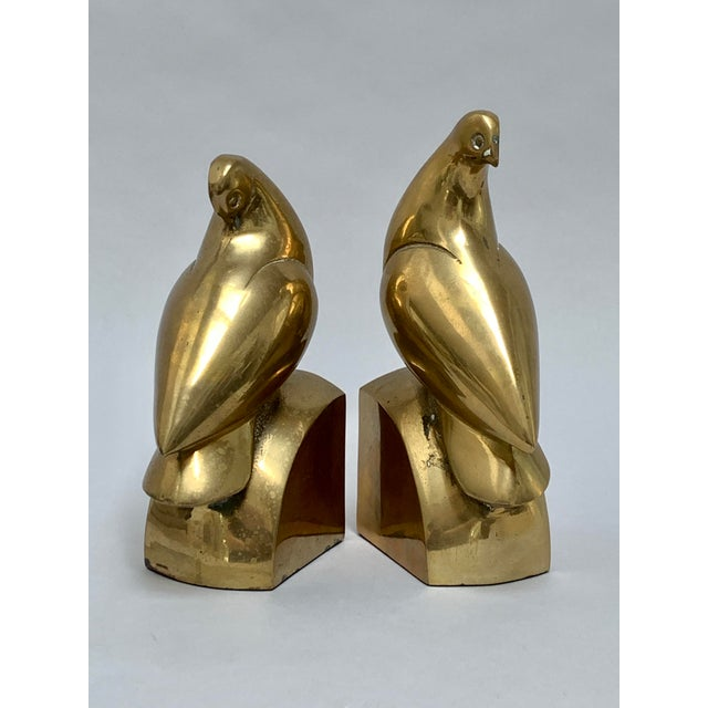 """Unique pair of brass doves in different poses perched atop thick curved brass bases. One bookend measures about 8"""" high x..."""