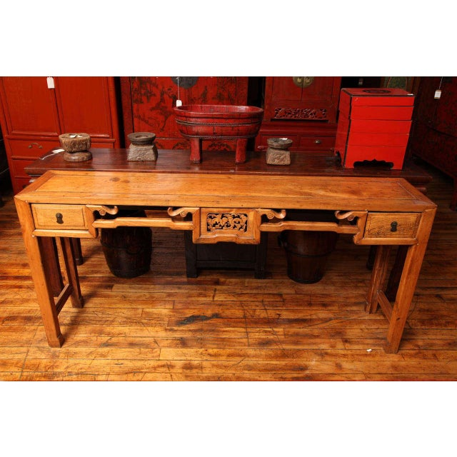 This Chinese, 19th century, narrow console table was made with natural elm, beautifully carved in the centre of the apron....