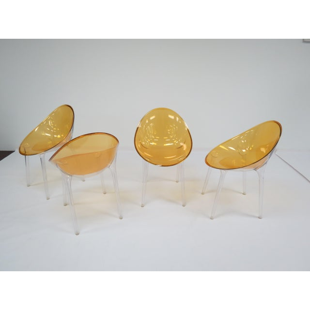 Set of four sleek-looking postmodern Mr. Impossible chairs in transparent ochre by Phillippe Starck for Kartell. Made in...