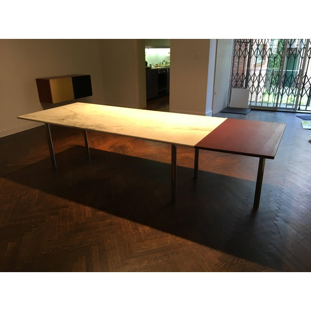 Large International style extension dining table with a beautifully figured Carrara marble slab sitting atop a steel...