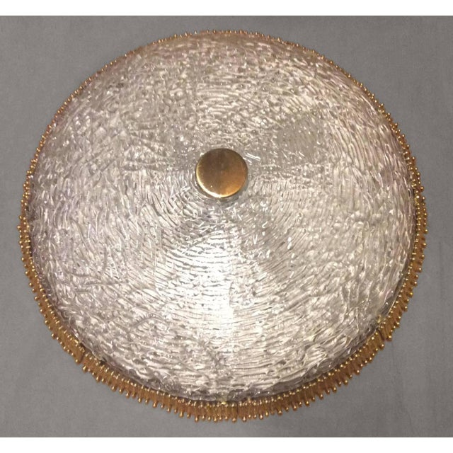 A flush mount textured clear glass fixture with circular textural brass detail by Hillebrand or Kaiser circa 1960's, 2...