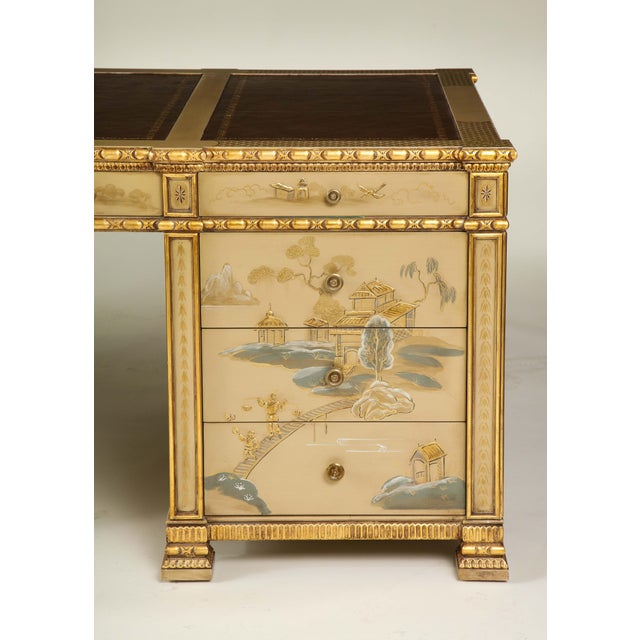 Handpainted overall on a warm beige-camel ground with gilt, blue, and white chinoiserie decoration including figures and...
