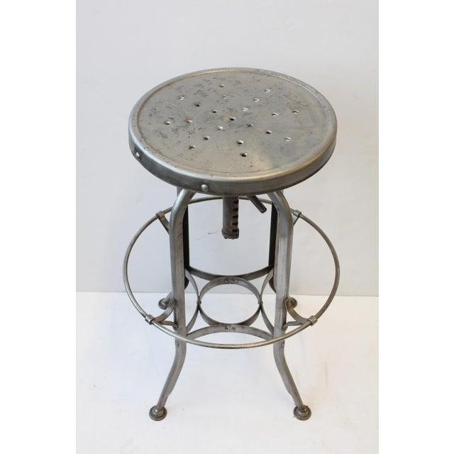 "1930s original American Industrial Toledo stool. Adjustable height 27.75-32"". Foot rest W 18.25"". Seat W 14.5""."