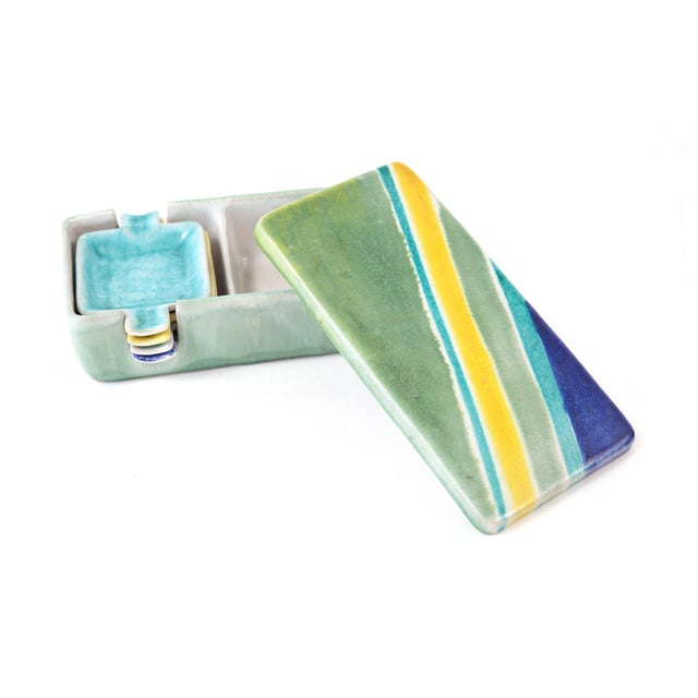 This celadon green ceramic box sporting vibrant stripes on its lid holds a set of four small individual cigarette ashtrays...