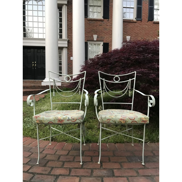 Pair of muted green iron bistro chairs with rope swag design, wooden tassels credited to Tomaso Buzzi and newer matching...