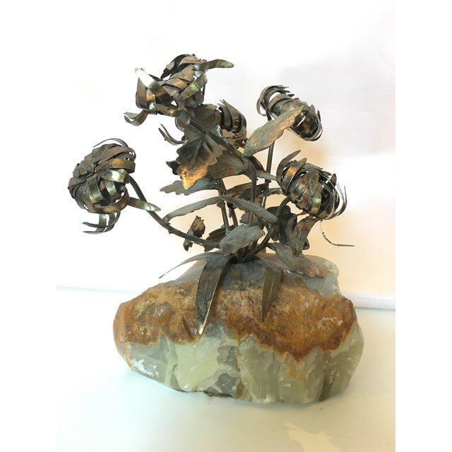 Brass flower sculpture mounted on solid quartz base.
