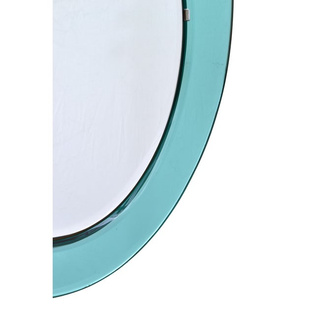 1960 Italian Fontana Arte oval Mirror by Max Ingrand. Two tone colored Mirror Glass on a wooden backing. Overall a classic...