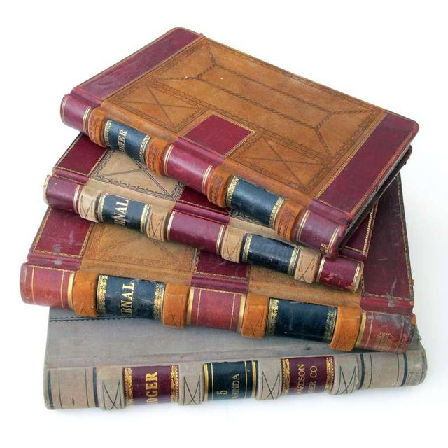 A large and unique set of 4 leather-bound accounting ledgers with gilt highlights; each large ledger dating to 1905 with...