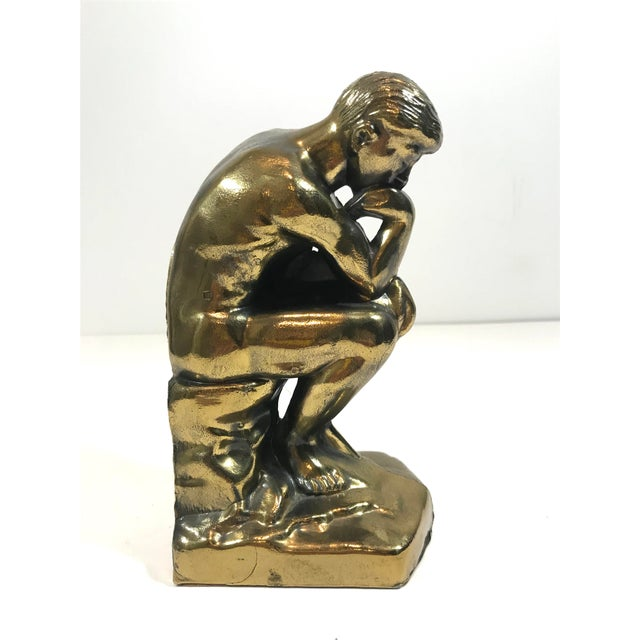 """Vintage bookend of Rodin's famous sculpture, """"The Thinker."""" Solid metal with an aged brass appearance, and felt bottom...."""
