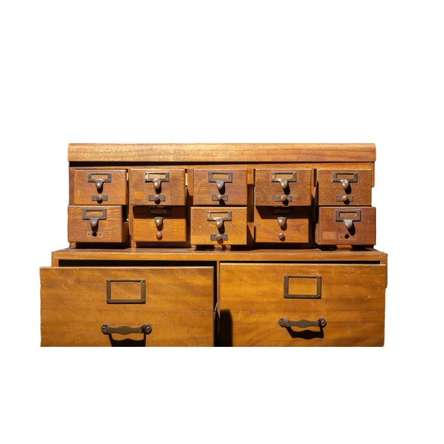 A mid-century modular card catalogue and file cabinet combo with a standing base. The steel interiors of the drawers are...