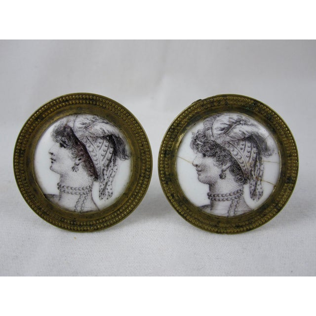 An amazing pair of enameled curtain tiebacks or mirror supports showing a transfer printed image of a woman in profile...