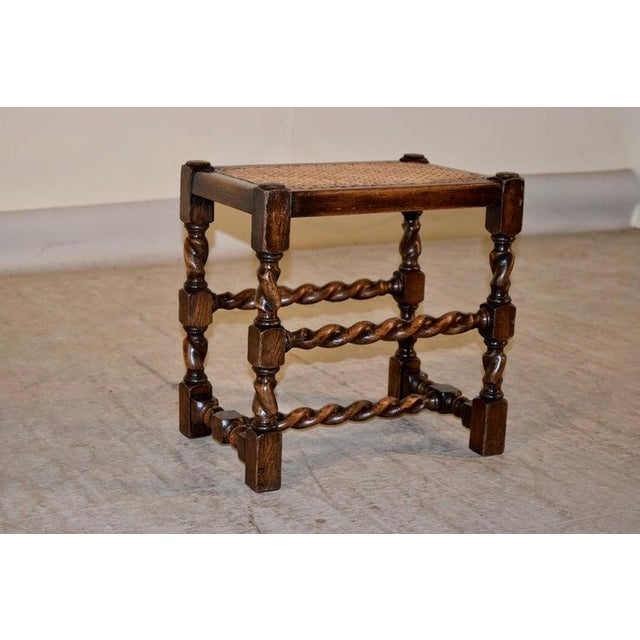 19th century English oak stool with hand-turned barley twist legs and stretchers and a woven cane top.