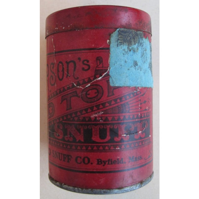 An lovely old snuff can with lid that was manufactured by Byfield Snuff Co. The can has a red background with black...