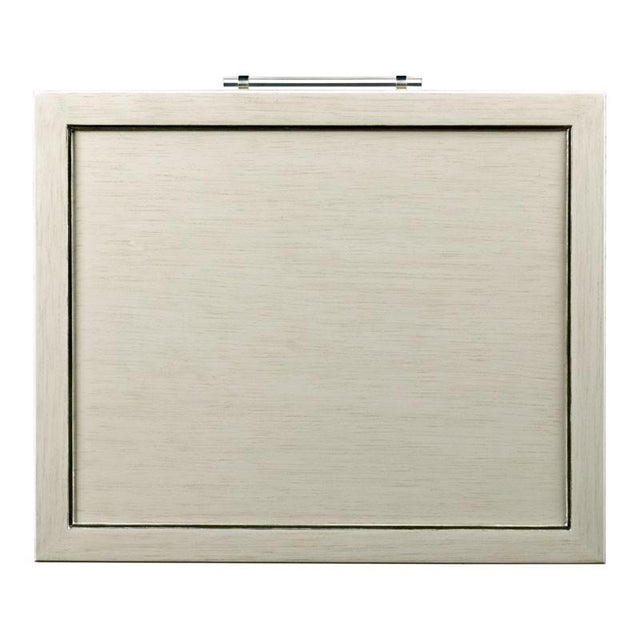 A rectangular framed top rests over four squared posts that flank a framed molded drawer accented by silver leaf stripes....