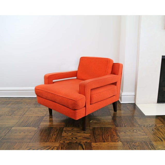 A lounge or club chairs with low arms and generous deep proportions upholstered in orange boiled wool raised on tapered...