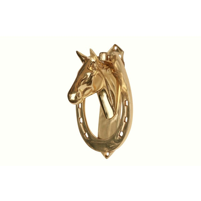 A solid brass horse head and horseshoe door knocker. A horse head bust on a flat back plate is attached to an oval knocker...