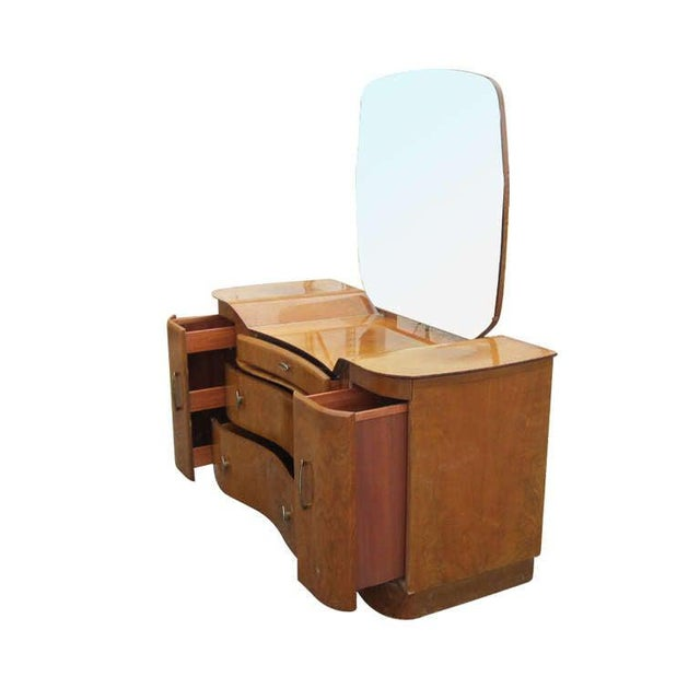 An Art Deco vanity made by Beautility featuring beautifully grained mahogany and a stylish flowing design. The dresser...