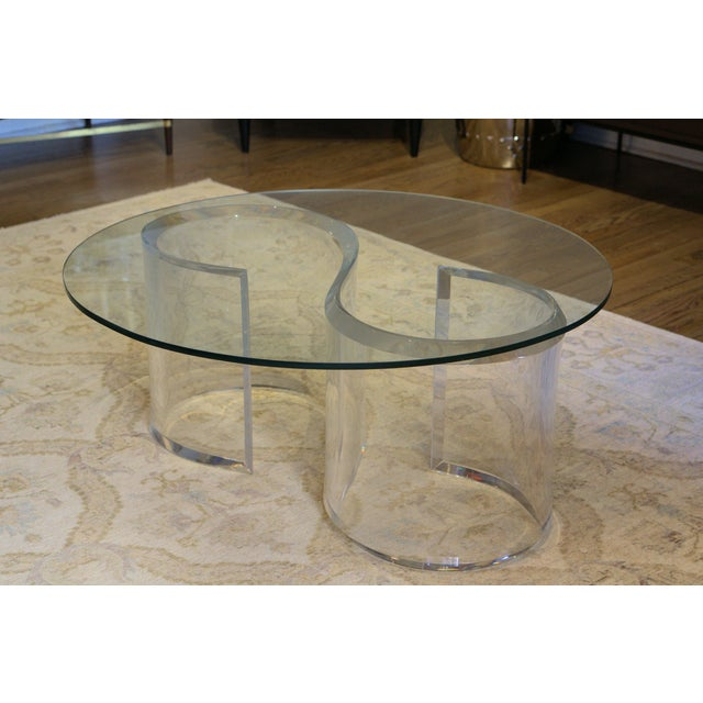 Beautiful mid-century modern coffee table with substantial S-shaped Lucite base and topped with a 36 inch round glass top....