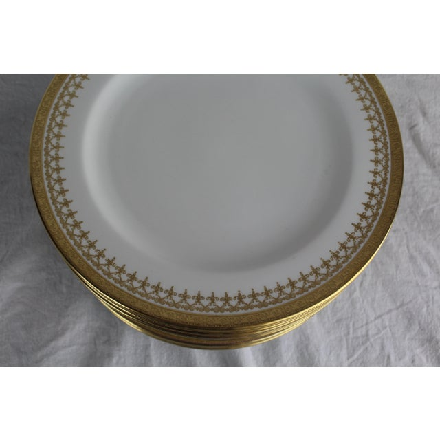 12 deep dish Cauldon England gold band plates with filagree inner border.