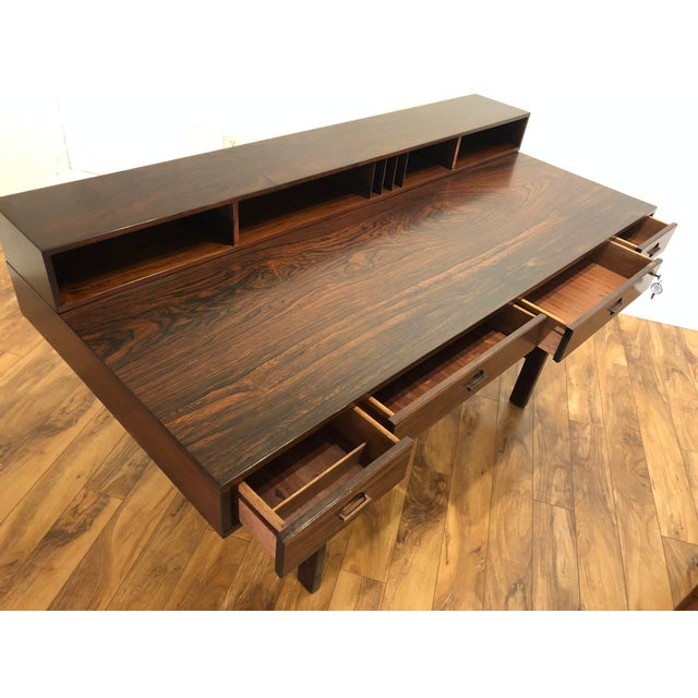 Rosewood desk by Peter Lovig Nielsen and Jens Quistgaard, made in Denmark. It has an innovative design with a hinged top...