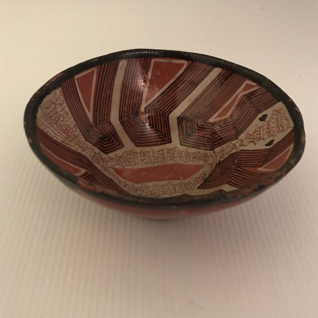 Hand painted red art pottery bowl with black rim.
