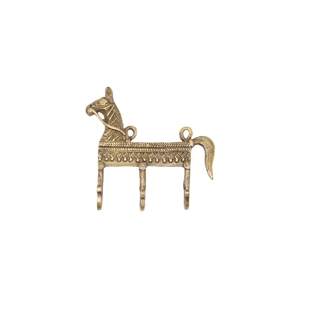 A bohemian brass wall hook fixture with three hooks. A central bar is cast with a horse head and tail decorated throughout...