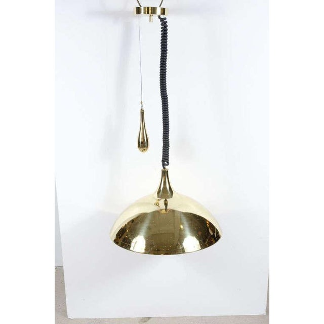 The 'Finlandia', mod. no. 214, a pendant light comprising a perforated polished brass dome shaped ceiling fixture with...