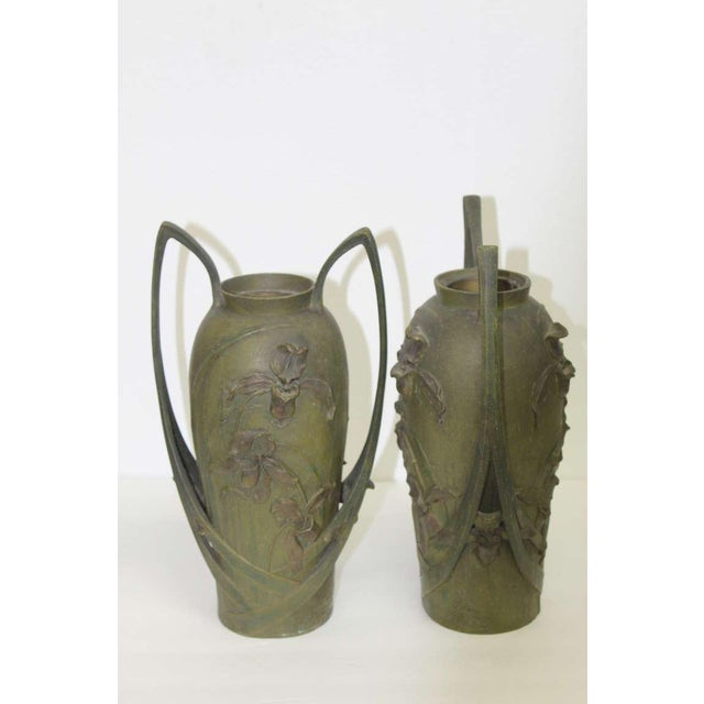 Pair of circa 1902, Art Nouveau vases with a two color patina bronzed surface. Cast in spelter metal, these vases are by...