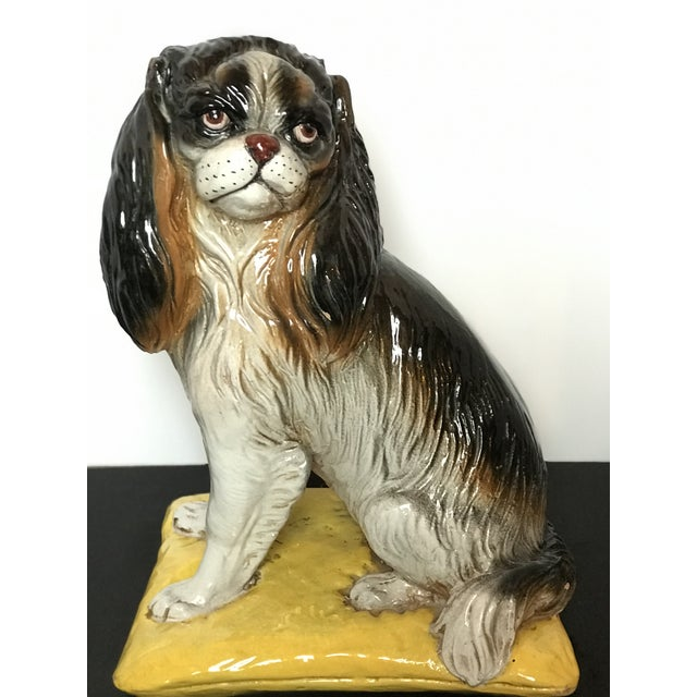 Vintage Italian glazed terra cotta sculpture of a tri-color King Charles Spaniel sitting on a bright yellow cushion....