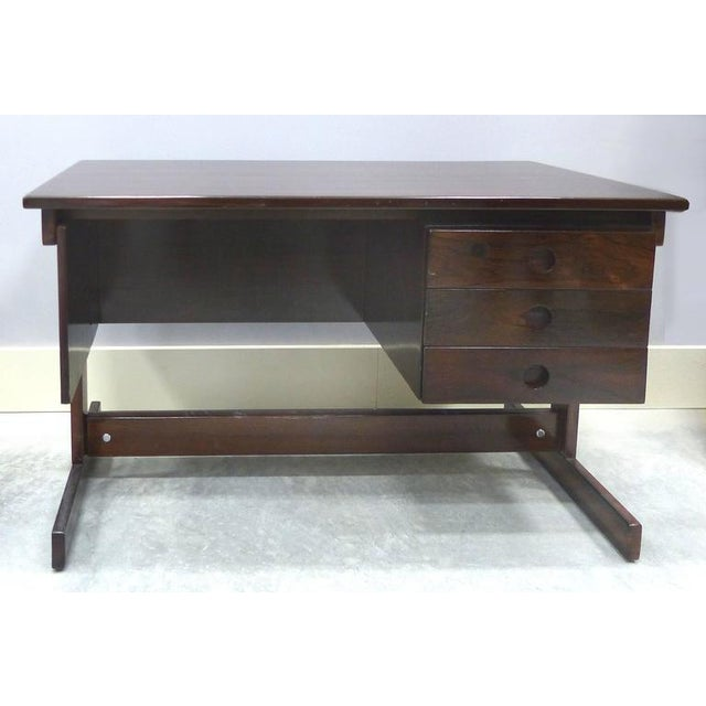 Offered is a three-drawer Jacaranda wood writing desk by master cabinet maker Joaquim Tenreiro, circa 1950. In unrestored,...