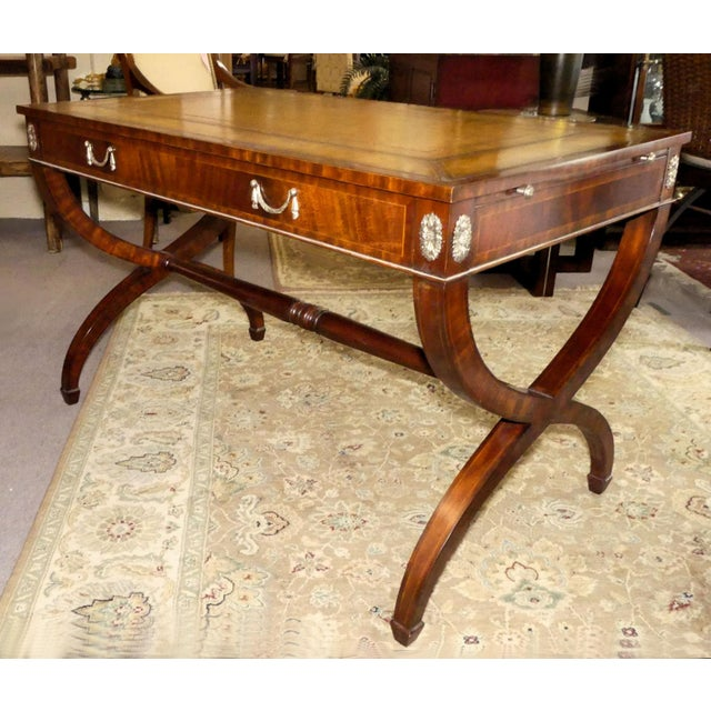 Maitland Smith leather top mahogany writing desk. Features graceful Regency styling with curved x-shaped legs joined by a...