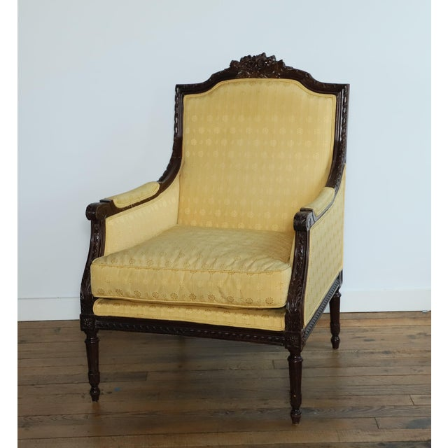 Absolutely lovely ornately carved dark mahogany vintage bergere or club chair in a custom soft yellow upholstery from 30th...