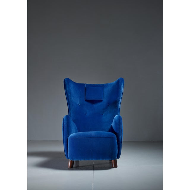 A 1940s wingback lounge chair attributed to Mogens Lassen. It stands on stained beech legs, round in front and rectangular...