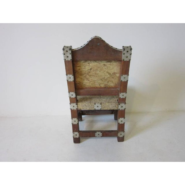 An African Royal or Prince chair with wood frame, animal skin seat and back embellished with nailed aluminum pieces and...