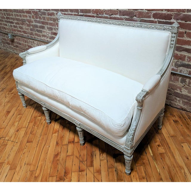 This is an elegant 19th Century settee with beautiful carved wood detail. The settee has been upholstered with white linen...