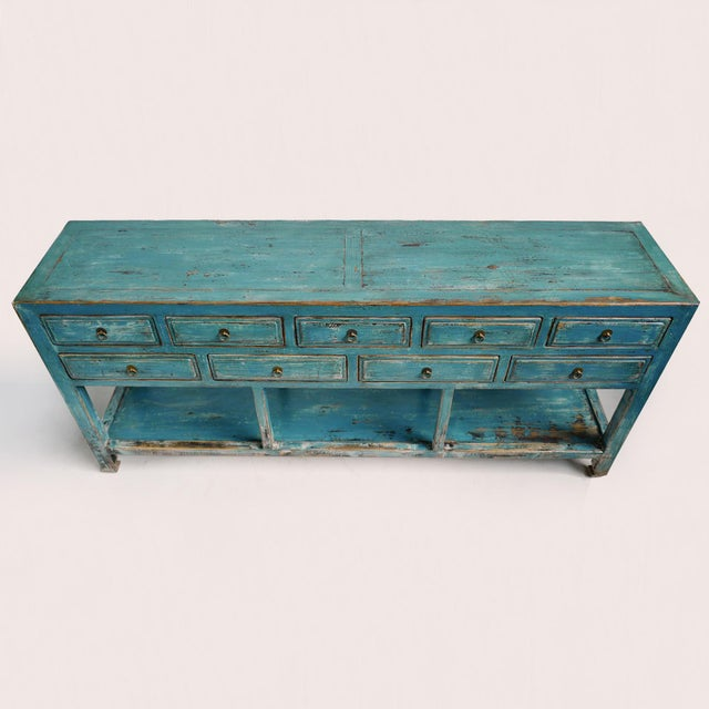 Beautiful blue lacquered nine drawer console table with open shelf below. Unique distressed finish with brass ring hardware.